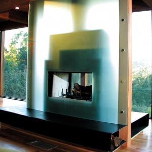 Fasada kominka zbudowana z płyty piaskowanego szkła sprawia, iż wpadające przez okno światło podkreśla kontury urządzenia ukrywając przy tym jego szczegóły. (fot. Alejandro Ortiz Architects Inc.)