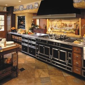 Bogato zdobione kuchnie La Cornue idealnie komponują się z ciężkimi meblami wykonanymi z ciemnego drewna