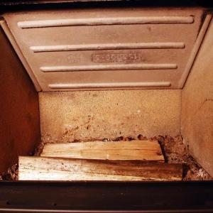 Na dno paleniska układamy równolegle dwa, trzy kawałki drewna (tego które będziemy normalnie używać do palenia).