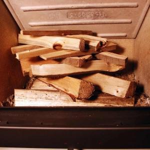 """Na ułożone w palenisku kawałki drewna układamy w kratkę szczapki drewna """"podpałkowego"""" tworząc prawdziwe """"indiańskie ognisko""""."""
