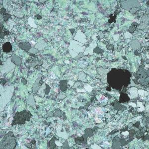 Rysunek 1. Zdjęcie otrzymane za pomocą mikroskopu polaryzacyjnego, przedstawiające drobnoziarnisty talkowo - magnezytowy steatyt MammuttiStone. Talk składa się z małych blaszek, mających zielony kolor na zdjęciu. Masa talku otacza ziarna magnezytu - koloru szarego na zdjęciu - które mają w przybliżeniu średnicę 0,5 mm. Zdjęcie wykonano z kierunku lineacji, to znaczy, że najdłuższy wymiar talku oraz szarych ziaren magnezytu jest skierowany zgodnie z kierunkiem, z którego wykonano zdjęcie.